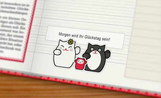Foto vom Lily Lux Notizbuch mit Winkekatzen und dem Zettel aus einem Glückskeks – morgen wird Ihr Glückstag sein!